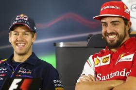 Red Bull Racing's German driver Sebastian Vettel (L) chats with Ferrari's Spanish driver Fernando Alonso (R) during the press conference at the Yas Marina circuit in Abu Dhabi on November 20, 2014.