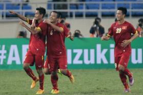 Vu Minh Tuan (left) celebrates after scoring Vietnam's first goal against Laos.