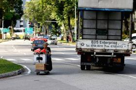 CLOSE SHAVE: A truck narrowly misses Madam Po (above), a seasoned cardboard collector. She, like other seniors in the area, seem unconcerned about the danger posed by traffic.
