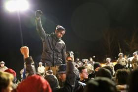 Demonstrators protest outside the Ferguson police station as soldiers with the Missouri National Guard stand watch.