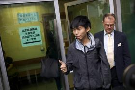 Joshua Wong gives a thumbs up as he exits a courthouse with his lawyer Michael Vidler after he was released on bail on Thursday.