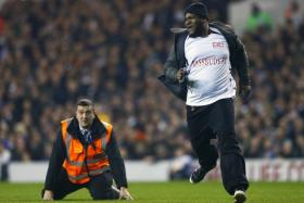 A steward falls over as he tries to catch a spectator that had run onto the pitch during the Europa League soccer match between Tottenham Hotspur' and Partizan Belgrade at White Hart Lane in London.