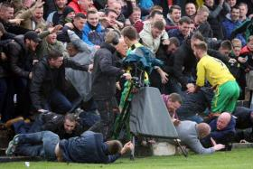A goal sent 300 fans of Welsh club Caernarfon Town rushing forward, causing a stadium wall to crumble.