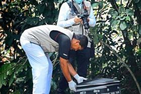 Penang Hospital forensic personnel taking the bag with body part to the hospital for a post mortem last month (Nov).