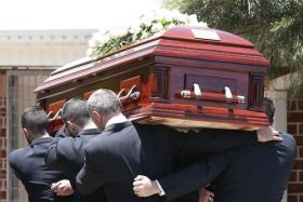 The coffin of Australian cricketer Phillip Hughes is carried into a hall before his funeral service in his home town of Macksville.