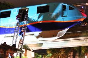 Two of the trapped passengers climb down from the stranded monorail train.