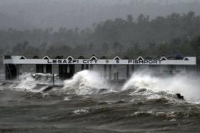 High waves brought about by strong winds pound a fishport building, hours before Typhoon Hagupit passes near the city of Legazpi on December 7, 2014