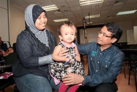 Dr Azmi (right) with Madam Nurul Wahida (left), who is holding Nurfatiha. The little girl has undergone a dozen operations to enable her to sit up straight.