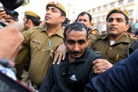 Indian police escorting Uber taxi driver and accused rapist Shiv Kumar Yadav (centre) following his court appearance in New Delhi on Dec 8.