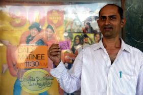 A man posing with his movie ticket ahead of a screening of the popular Bollywood Hindi film 'Dilwale Dulhania Le Jayenge' (The Brave hearted Will Take The Bride Away) at the Maratha Mandir cinema in Mumbai.