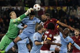 7 Joe Hart (in green) made seven saves and claimed one cross against Roma.