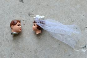 Heads from a broken bride and groom cake topper.