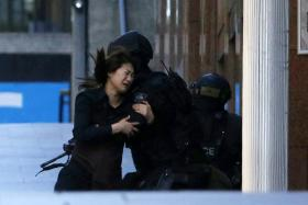 A hostage running towards a police officer outside Sydney cafe, where hostages are being held by a gunman.