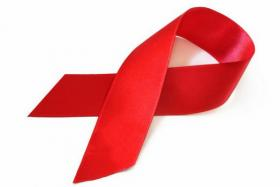The red ribbon, a symbol of awareness and support for those living with HIV.