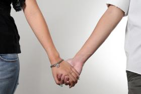 Posed photo of a couple holding hands.