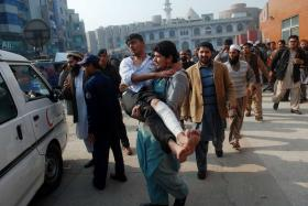 A man carrying a student, who was injured during an attack by Taliban gunmen on the Army Public School.
