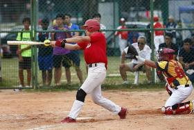 HIT IT: Singapore (in red) kicking off their Asian Men's Championship Qualifier 2015 against Brunei at the Kallang Softball Diamond yesterday.