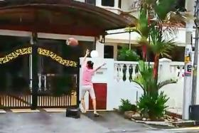 A screen grab from the video showing the woman hurling an object onto the driveway of a neighbour's house.