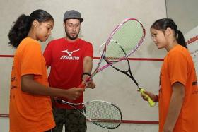 THIS IS THE WAY: National squash coach Ibrahim Gul, whose father Rahim was also a national coach, giving tips to Keertana Veerayah (left) and 