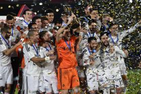 The Real Madrid team celebrate holding the cup of the 2014 FIFA Club World Cup at the Marrakesh stadium in the Moroccan city of Marrakesh on December 20, 2014.