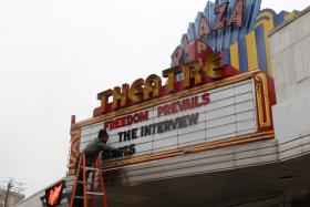 General Manager Brandon Delaney putting letters on the marquee sign announcing that the Plaza Theatre would be showing the movie The Interview beginning Christmas Day in Atlanta, Georgia.
