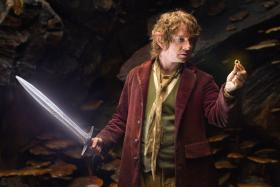 Martin Freeman as Bilbo Baggins in The Hobbit holding Sting, an elven sword that glows blue in the presence of orcs.