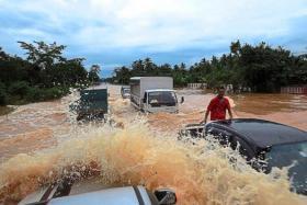 Motorists passing through the flooded Temerloh-Jerantut road near Kampung Tebing Tinggi in Kuala Krau, Pahang.