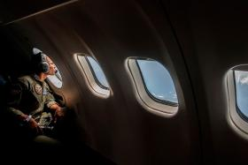 A member of the Indonesian military looking out of the window during a search operation for missing AirAsia flight QZ8501, over the waters of the Java Sea on Dec 29.