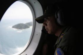 A crew member on an Indonesian Maritime Surveillance looks out the window during a search for AirAsia's Flight QZ8501.