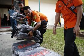 Search and rescue workers preparing to load body bags onto a flight to Kalimantan in Pangkal Pinang, Bangka Dec 30, 2014.