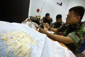 Army soldiers sit near a map of Belitung island while monitoring search operations for AirAsia flight QZ8501 at Halim Perdanakusuma airport in Jakarta.