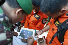 Indonesian military pilots look at a flight plan before setting out for a search mission for AirAsia's Flight QZ8501 in Pangkal Pinang