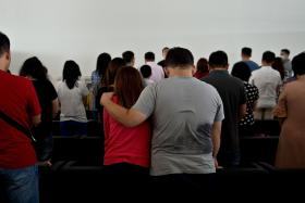 Family members of passengers of AirAsia flight QZ8501 praying inside a holding room at Juanda International Airport in Surabaya on Dec 31.