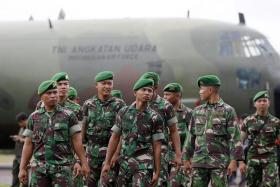 Indonesia army soldiers walking near a Hercules C-130 at Iskandar airbase in Pangkalan Bun as they wait for good weather before continuing with search operations.