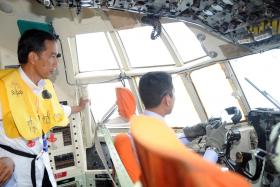 Indonesian President Joko Widodo (L) standing in the cockpit of an Air force aircraft Hercules C-130 during the search and locate (SAL) operation for missing AirAsia flight QZ8501.