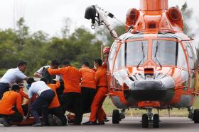 Indonesian Search and Rescue crews unload one of two bodies of AirAsia passengers recovered from the sea at the airport in Pangkalan Bun.