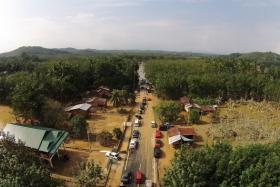 An aerial view of the flooded road in the village of Bonggol Nering. The road leads to the still flooded town of Kusial Baru.