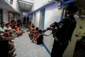 File photo taken on Dec 16, 2014 showing National Bureau of Investigation operatives rounding up inmates inside Bilibid Prison in Manila.