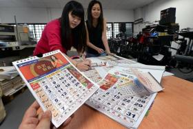 DETAILED: (Above) Ms Chew Fong Ling (left) and Ms Marie Tan checking the calendars for accuracy.