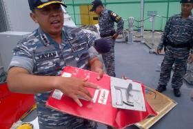 Indonesian Navy captain of 'KRI Bung Tomo' colonel Yayan Sofiyan holding wreckage from AirAsia flight QZ8501.