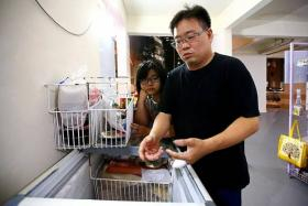 MISHAP: (Above) Mr Ng Hoe Ghee pointing to the freezer he was cleaning when he got frostbite. With him is his second daughter, Tarine.