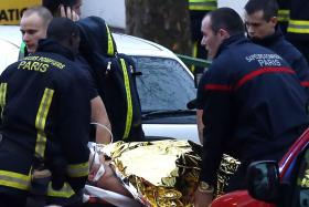 Rescue service workers and firefighters evacuate an injured person on a stretcher near the site of a shooting on Thursday evening (local time) in Montrouge, south of Paris.