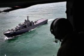 CHOPPY WATERS: The view of the RSS Persistence from above, inside the Super Puma helicopter.