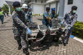 Members of the Indonesian Navy carry wreckage recovered from the Java Sea of AirAsia flight QZ8501 upon its arrival at Juanda military airport in Surabaya.
