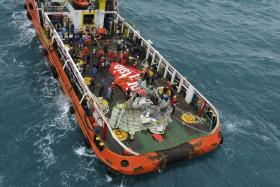 The tail of the AirAsia QZ8501 passenger plane lies on the deck of the Indonesian Search and Rescue (BASARNAS) ship Crest Onyx after it was recovered at sea on Jan 10.