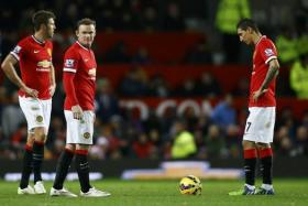 Manchester United players (L-R) Michael Carrick, Wayne Rooney and Angel Di Maria react after conceding a goal to Southampton.
