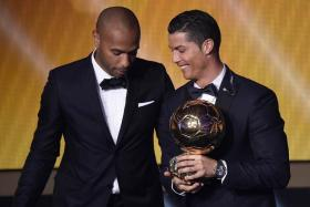 Cristiano Ronaldo receives the Ballon d'Or trophy from Thierry Henry.
