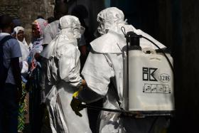 File photo of Red cross workers, wearing protective suits, getting ready for the funeral of an Ebola victim i