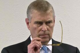 Britain's Prince Andrew puts on his glasses before giving a speech to business leaders during a reception on the sidelines of the World Economic Forum in Davos.