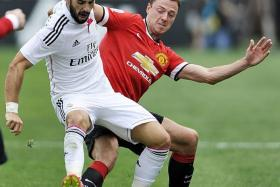 FINANCIAL HEAVEN: United's Jonny Evans (in red) and Real's Alvaro Arbeloa competing at the Guinness International Champions Cup last year. The Red Devils can overtake the Spanish giants at the top of the money league if they return to Champions League action next season.